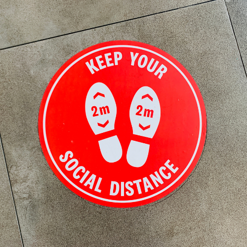 red social distance sign on the floor
